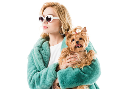 Young girl in fur coat with fluffy dog isolated on white