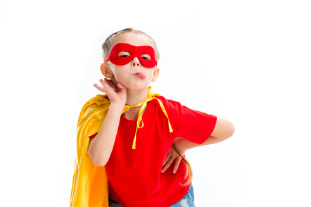 Supergirl wearing yellow cape and red mask for eyes showing tongue isolated on white Stock Photo