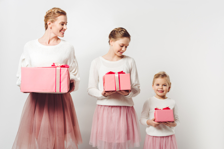 smiling mother and little daughters in similar pink tutu tulle skirts with wrapped gifts isolated on grey Stock Photo