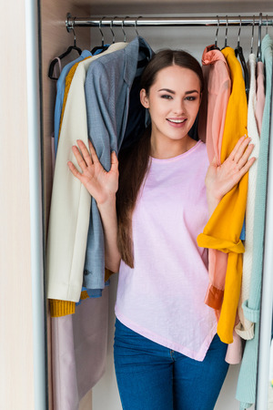 smiling young woman standing between hanging clothes in cabinet at home Stock Photo