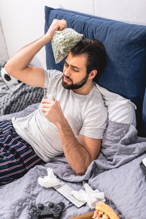 loner having headache with hangover and touching head with frozen green beans in bedroom