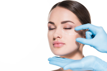 doctor touching face of young woman with dotted line for plastic surgery isolated on white Foto de archivo - 111594248