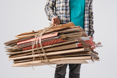 cropped shot of man holding pile of folded cardboard boxes isolated on grey, recycling concept Archivio Fotografico - 111594252