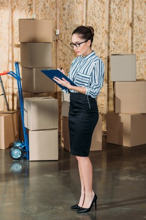 Young businesswoman writing in clipboard by stacks of delivery boxes Reklamní fotografie