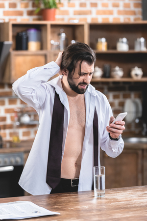 handsome loner businessman with hangover looking at smartphone at kitchen Stock Photo