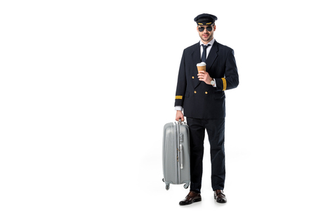 young pilot in uniform and sunglasses with coffee to go and luggage isolated on white Stok Fotoğraf