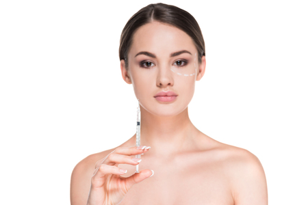 beautiful young woman with dotted line drawn on face for plastic surgery holding syringe isolated on white Foto de archivo - 111594411