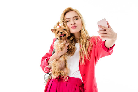 Young girl wearing pink suit holding cute Yorkshire terrier and taking selfie isolated on white