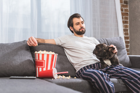 handsome loner sitting with bulldog on sofa and eating popcorn in living room