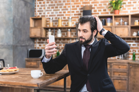 handsome loner businessman taking selfie with smartphone at kitchen Stock Photo