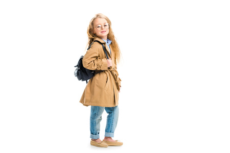 513394032e52 Side view of kid in glasses holding bag and wearing beige trench coat  isolated on white