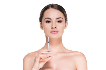 attractive young woman with dotted line drawn on face for plastic surgery holding syringe isolated on white