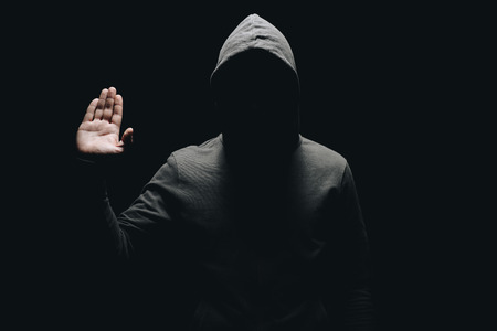 unrecognizable man in hoodie showing palm isolated on black