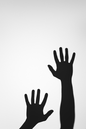 scary mysterious shadows of human hands on grey Stockfoto