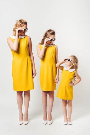 stylish mother and daughters in similar retro style yellow dresses looking at each other on white