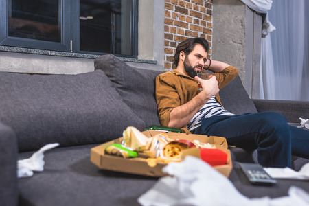 irritated loner sitting on sofa with glass of whiskey in dirty living room Stock Photo