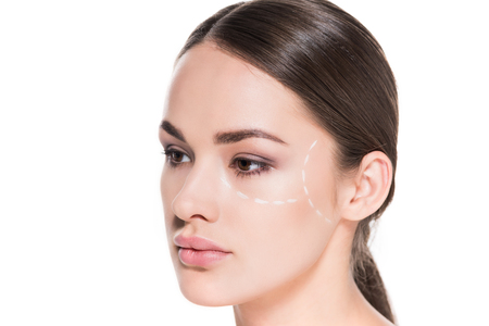 attractive young woman with dotted line drawn on face for plastic surgery isolated on white Foto de archivo - 111595319
