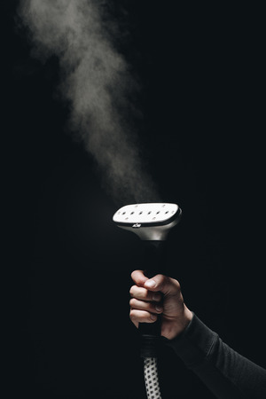 close-up partial view of person holding garment steamer with steam on black Standard-Bild - 111595877