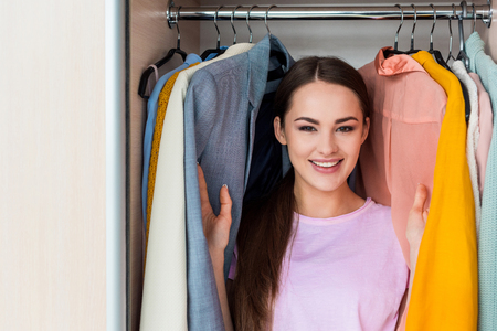 happy young woman standing between hanging clothes in cabinet at home Stock Photo