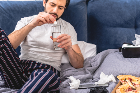 loner having headache with hangover and putting pill into glass of water in bedroom