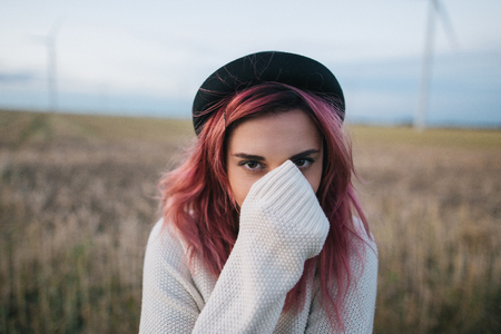 beautiful girl with pink hair in white sweater and hat standing in field