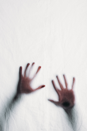 blurry silhouette of human hands touching frosted glass Reklamní fotografie - 111595903