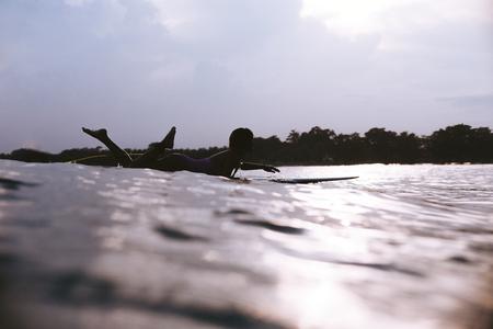 silhouette of sportswoman lying on surfing board in ocean on sunset