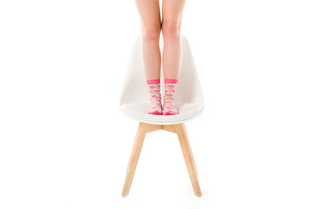 Female legs in pink socks standing on chair isolated on white Banque d'images