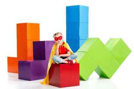 Supergirl wearing yellow cape and red mask for eyes sitting on cube isolated on white