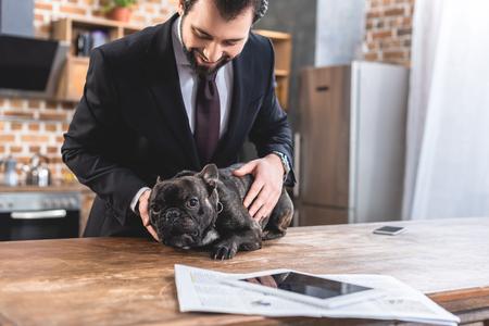handsome loner businessman palming bulldog on kitchen counter at kitchen