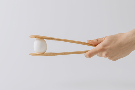 cropped image  of hand holding wooden tongs with white egg