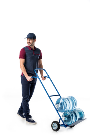 smiling delivery man in uniform pushing hand truck with large bottles of water isolated on white