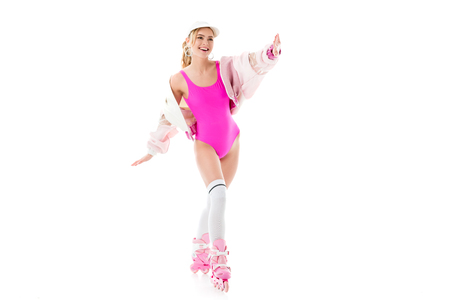Blonde woman in pink swimsuit having fun on roller skates isolated on white Stock Photo