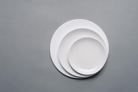 Placas blancas de diferentes tamaños sobre fondo gris