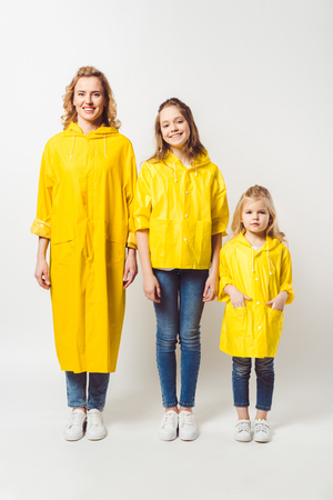 mother and daughters in yellow raincoats on white