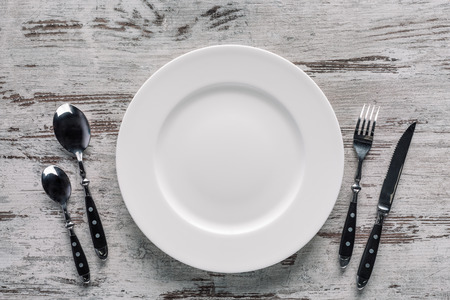 White plate and silverware on rustic wooden background