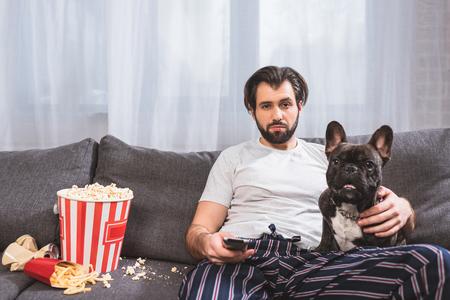 Hermoso solitario viendo la televisión con bulldog en el sofá de la sala de estar