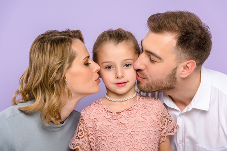 Parents kissing daughter isolated on violet Banque d'images