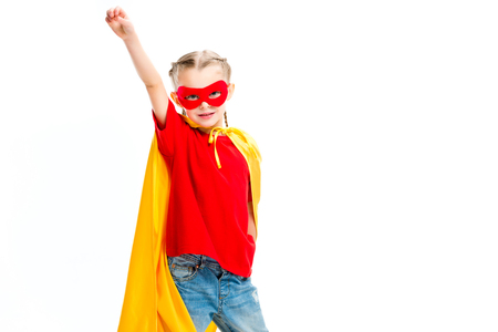 Supergirl wearing yellow cape and red mask for eyes gesturing by hand isolated on white Stock Photo