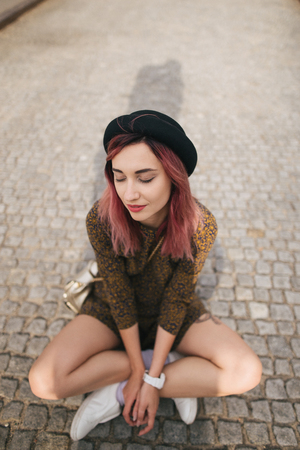 girl with closed eyes in trendy dress and hat sitting on pavement in city