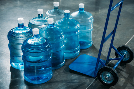 Delivery cart placed by water bottles 스톡 콘텐츠