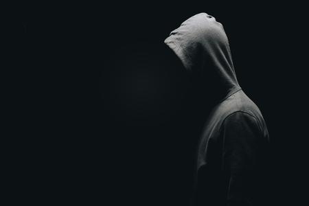 Vista lateral del hombre irreconocible en el hombre de pie aislado en negro