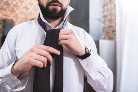 cropped image of loner businessman tying necktie at kitchen Stock Photo
