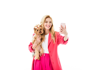 Attractive young woman dressed in pink holding cute dog and taking selfie isolated on white