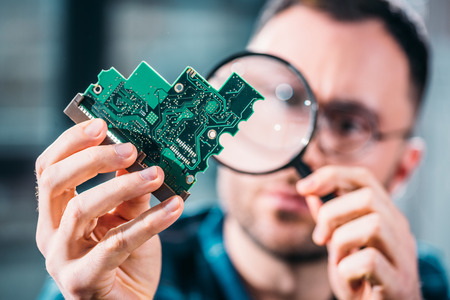 Close-up view of man looking at circuit board through magnifying glass Stock fotó