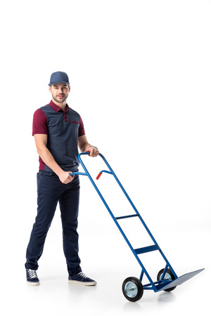 delivery man in uniform with empty hand truck isolated on white