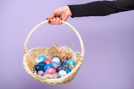 Woman holding Easter basket with colored eggs isolated on violet