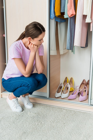 thoughtful young woman sitting near cabinet and looking at shoes