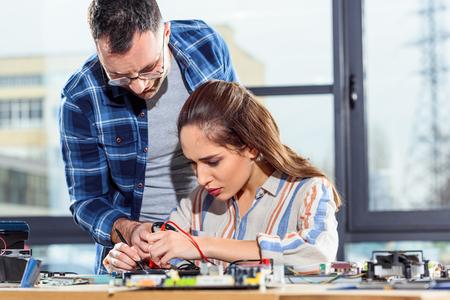 Woman and man engineers testing circuit board