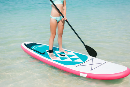 cropped view of woman on stand up paddle board on sea at tropical resort 版權商用圖片